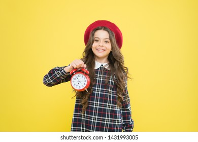 Putting her alarm clock on. Happy little girl holding alarm clock on yellow background. Small child smiling with mechanical clock. Wakeup clock.