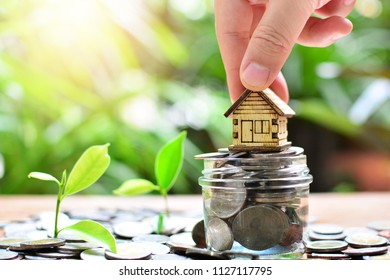putting house model on coins saving for concept investment mortgage fund finance and home loan
