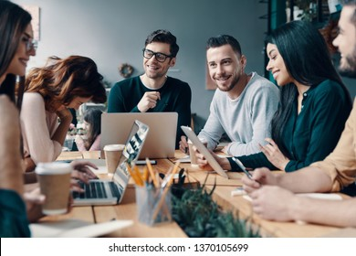 Putting ideas into something real. Group of young modern people in smart casual wear discussing something and smiling while working in the creative office