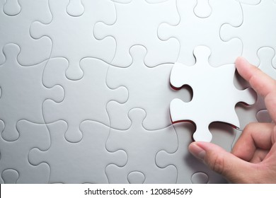 Putting last jigsaw puzzle piece. Solving and completing the task.