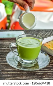putting milk  into glass green tea latte on wood table.A cup of green tea matcha latte.