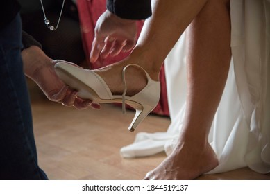 Putting on wedding shoes with helping hands of assistant.