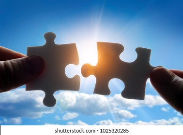 Putting puzzle pieces together on sky background with sunlight