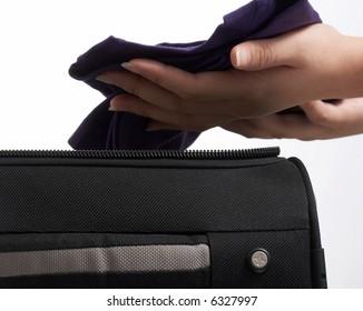putting a shirt on a travel bag