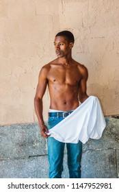 Putting shirt on. Young African American Man with short hair, wearing blue jean, half naked, showing slim fit body, holding white shirt, standing painted wall on street in New York in hot summer.