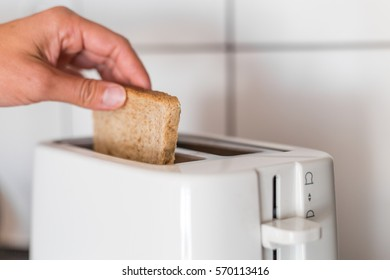 Putting a slice of bread to the toaster