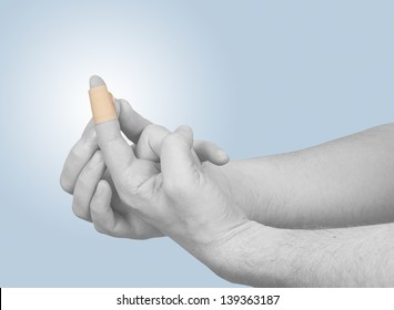 Putting a small adhesive plaster on a finger.  Concept photo with Color Enhanced skin.