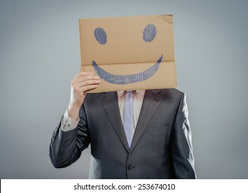 Putting a smiling face on. Man holding cardboard paper with smiley face printed on as happiness and joy concept.