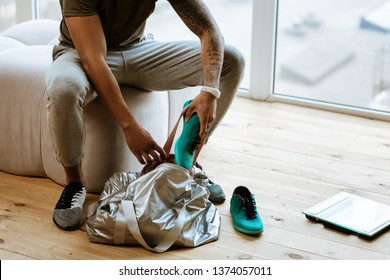 Putting sneakers. Close up of dark-skinned sportsman with tattoo putting sneakers into bag before going to gym