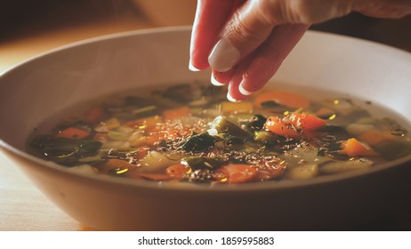 Putting spices on minestrone soup. Vegetarian soup dish is on table. Vegetarian healthy meal for dinner. Ready vegetable meal for lunch, hot and cozy soup for dinner at home.