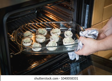 putting stuffed mushrooms with blue cheese in the oven