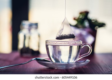 Putting tea bag into glass cup full of hot water