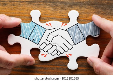 Putting together handshake jigsaw puzzle pieces on wood desk. Concept image of business partnership and collaboration.