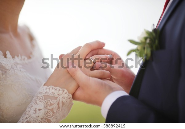putting a wedding ring on bride's finger at wedding ceremony