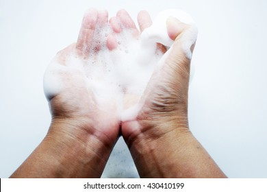 Putting whip foam soap bottle with foam in hands on blue-gray background.