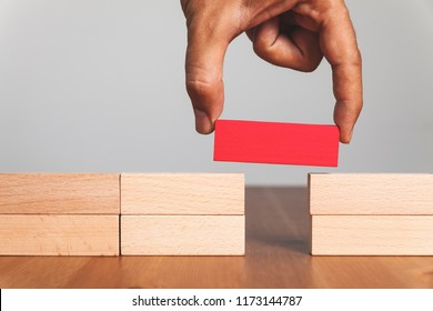 Putting a wooden block between gap, business concept