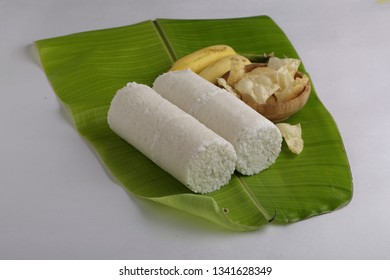 puttu soth indian breakfast-side view of two slices of puttu with banana and pappadam on a tender banana leaf with white background