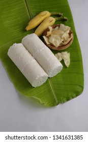 puttu south indian breakfast-top view of two slices of puttu with banana and pieces of pappadam on atender banana leaf with white background