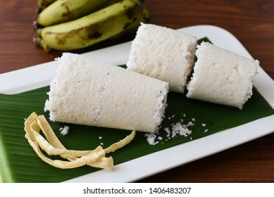 Puttu or white Pittu, top view of popular South Indian steamed breakfast dish made of rice flour,  grated coconut in bamboo mould with banana and Pappad Kerala, India. Sri lankan food on banana leaf.