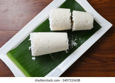 Puttu or white Pittu, top view of popular South Indian steamed breakfast dish made of rice flour and grated coconut in bamboo Puttu Kutti vessel Kerala, India. Sri lankan food on banana leaf.
