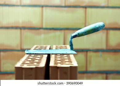 A putty knife or mason's trowel resting on a stack of bricks after a construction of a wall in the background. Inside of a building site at the end of a masonry work.