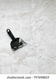 Putty knife and wall covered with texture putty