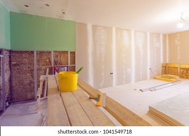 Putty knife, yellow bucket with glue and glue rollers on the wooden board in room  is under construction, remodeling, renovation, extension, restoration and reconstruction.