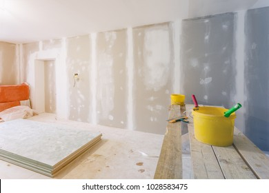 Putty knife, yellow buckets with glue and glue rollers on the wooden board in room  is under construction, remodeling, renovation, extension, restoration and reconstruction.
