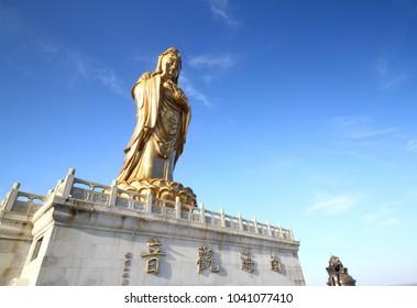 Putuoshan / China – April 11,2011 : Big golden Guan Yin statue with blue sky at Putuoshan, China