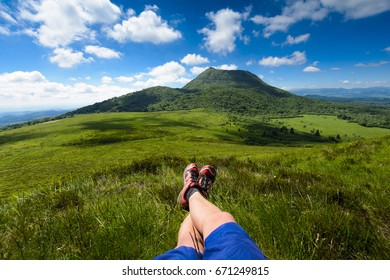 Puy de Dome mountain and hikers legs, Auvergne, France