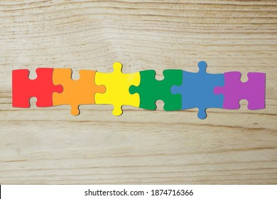 A puzzle with 6 pieces with the colors of the lgtb flag joined together. wooden background