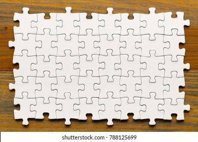 Puzzle background. White pieces on wooden table. Partially completed box shaped pzzle pieces.