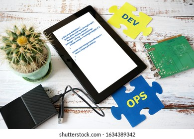 puzzle with Dev and Ops words near laptop and motherboard. DevOps Concept for software engineering culture and practice of software development and operation