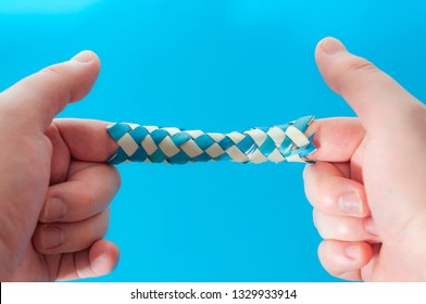 Puzzle game and logic games concept with hands playing with a chinese finger trap, a toy that the more you pull the tighter it gets stuck and you need to push to escape isolated on blue background