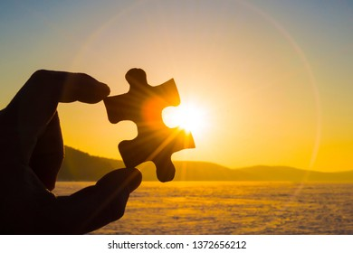 Puzzle in the hand against the background of the evening sun, sky. Sunset. detail. part. Business idea concept. teamwork,