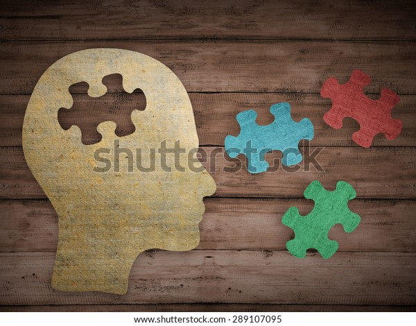 Puzzle head brain concept. Human head profile made from brown paper with a jigsaw piece cut out. Choose your personality that suit you