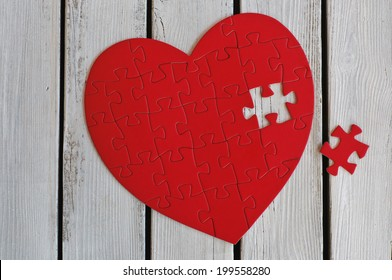 Puzzle heart on wooden background
