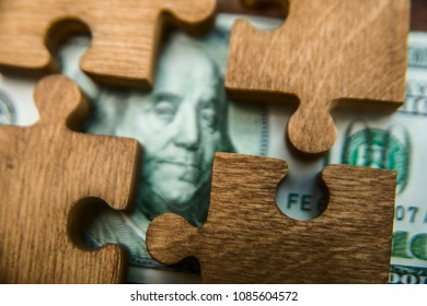 puzzle from hundred dollar bills on a wooden background. portrait of american president.