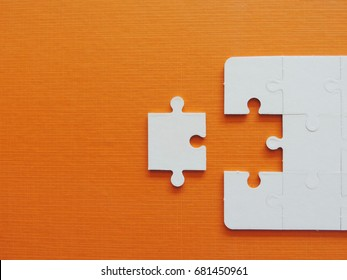 Puzzle jigsaw on orange background.