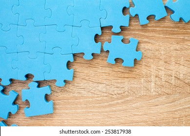 Puzzle on wooden background.Team business concept