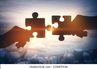 Puzzle piece silhouette on blurry city backdrop. Teamwork and jigsaw concept. Double exposure
