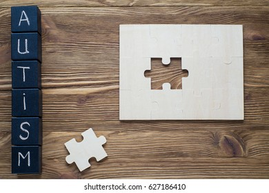 Puzzle pieces and black wooden cubes with word AUTISM on wooden background, top view, flat lay. Autism Spectrum Disorder (ASD).  Autism awareness. Concept of autism word.