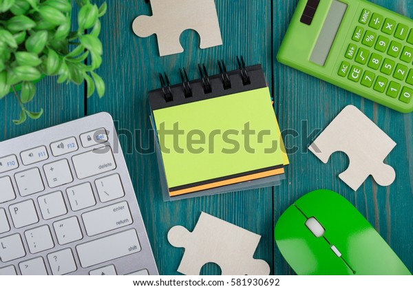 Puzzle pieces, calculator, sketchbook, computer keyboard and mouse on a blue wooden background