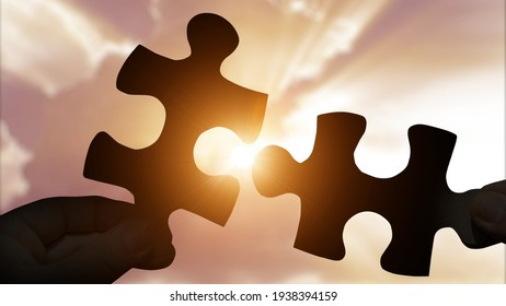 Puzzle pieces connecting with hands on sunset background