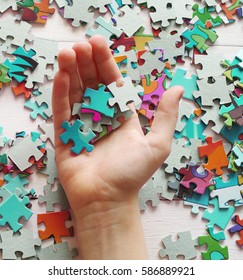 Puzzle pieces in the hand of a child closeup, top view