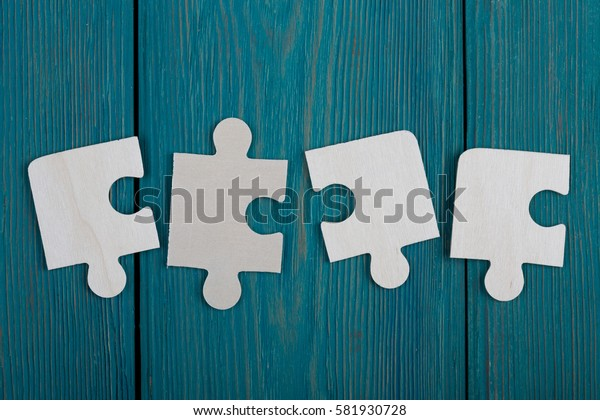 Puzzle pieces on a blue wooden background