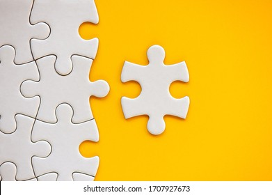 Puzzle pieces on orange background. White square puzzle pieces grid. Business background. Copy space for text, top view, close up.