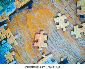 puzzle pieces on a wooden table. Not assembled puzzle