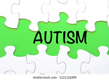 Puzzle pieces with word AUTISM on green background, top view, flat lay. Autism Spectrum Disorder (ASD). Autism awareness. Concept of autism word.