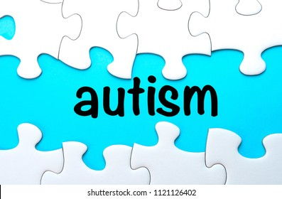 Puzzle pieces with word AUTISM on blue background, top view, flat lay. Autism Spectrum Disorder (ASD). Autism awareness. Concept of autism word.